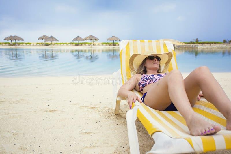 Härlig kvinna som kopplar av i en vardagsrumstol på en tropisk strandsemester royaltyfria bilder