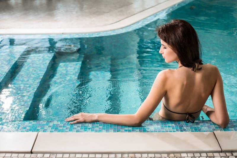Härlig kvinna som kopplar av på den lyxiga poolsiden Flicka på pölen för loppbrunnsortsemesterort arkivbilder