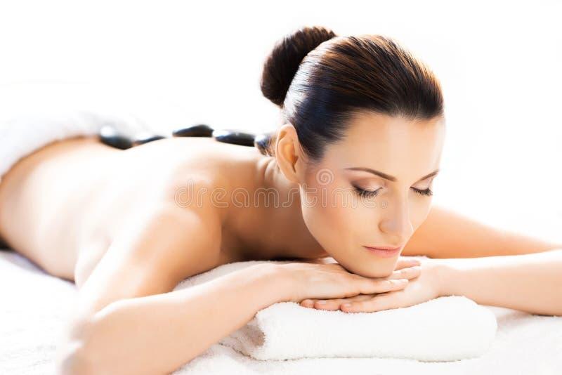 Härlig kvinna som lägger på ett mattt i massagesalong arkivbilder