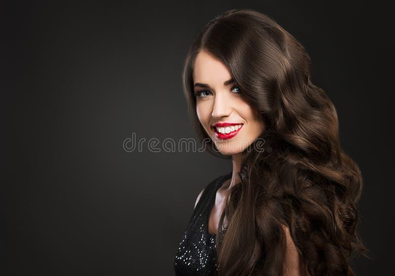 Härlig kvinna som ler, glamourstående på mörk bakgrund arkivbilder