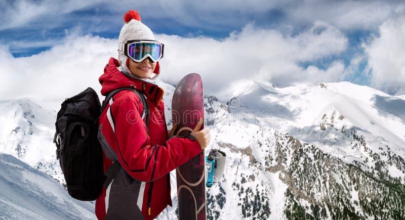 Härlig kvinna som ler och rymmer en snowboard arkivfoto