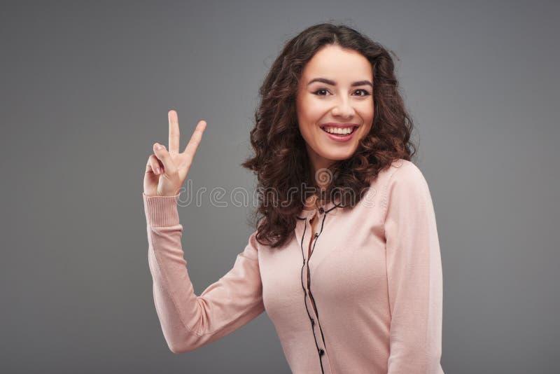 Härlig kvinna som ler och visar segertecknet arkivfoto