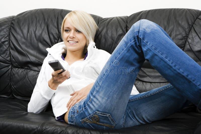Härlig kvinna som ler, som hon håller ögonen på television fotografering för bildbyråer