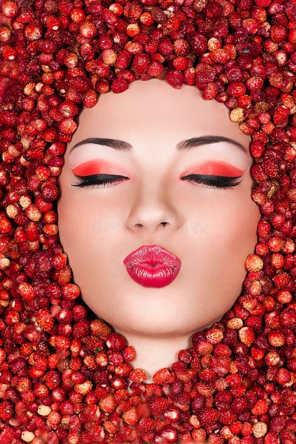 Härlig kvinna som ligger i lös jordgubbe arkivbilder