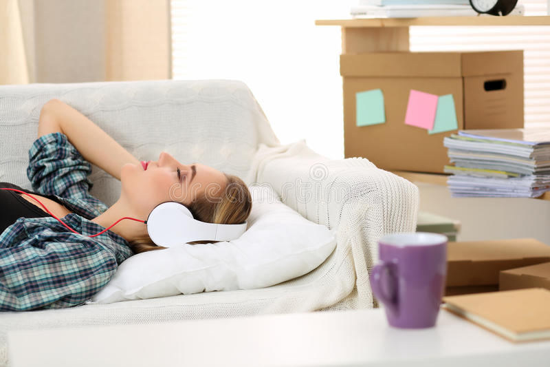 Härlig kvinna som ligger på bärande hörlurar för vit soffa arkivbilder