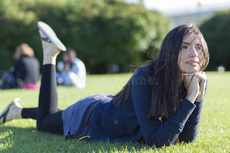 Härlig kvinna som ligger på gräs arkivfoto