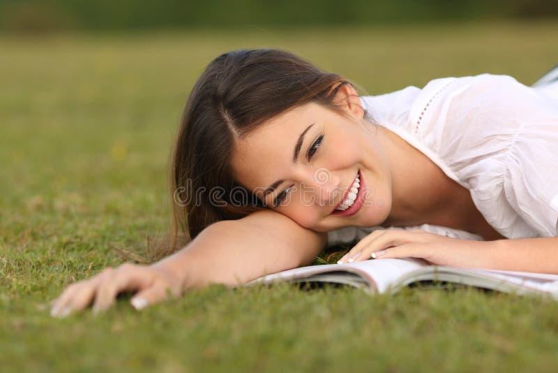 Härlig kvinna som ligger på gräset som läser en pappers- bok fotografering för bildbyråer