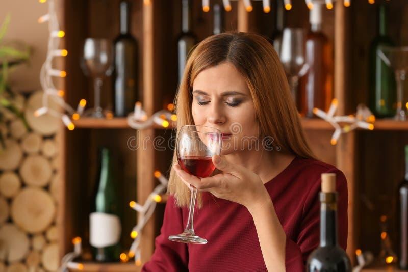 Härlig kvinna som luktar arom av rött vin i stång arkivbilder