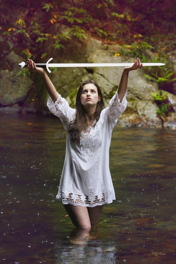 Härlig kvinna som lyfter ett svärd till himlen arkivbilder