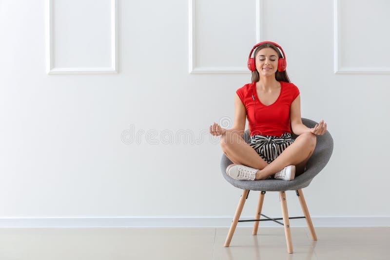 Härlig kvinna som lyssnar till musik, medan meditera i fåtölj nära den vita väggen arkivfoto