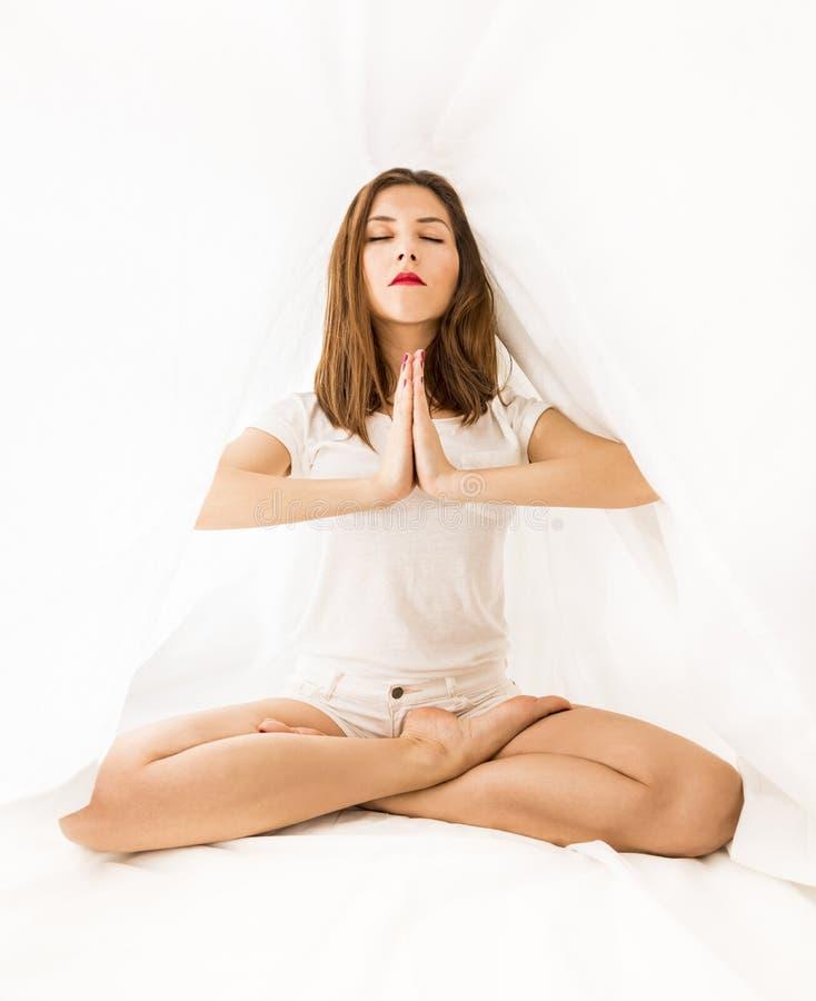 Härlig kvinna som mediterar i sovrummet royaltyfria bilder