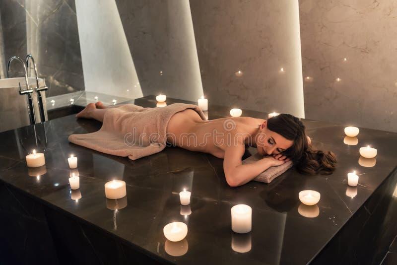 Härlig kvinna som ner ligger på massagetabellen i lyxig wellnessmitt arkivfoto