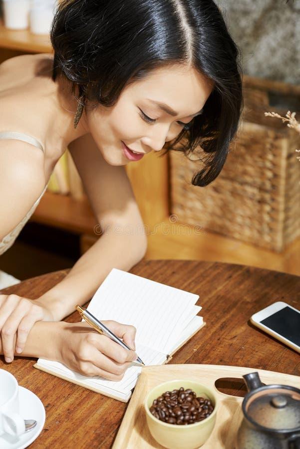 Härlig kvinna som ner skriver plan arkivfoto