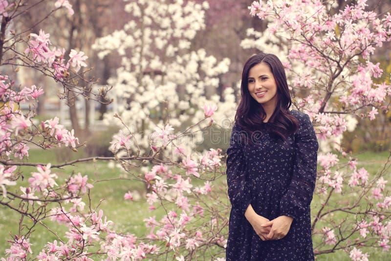 Härlig kvinna som omges av blommor royaltyfria bilder