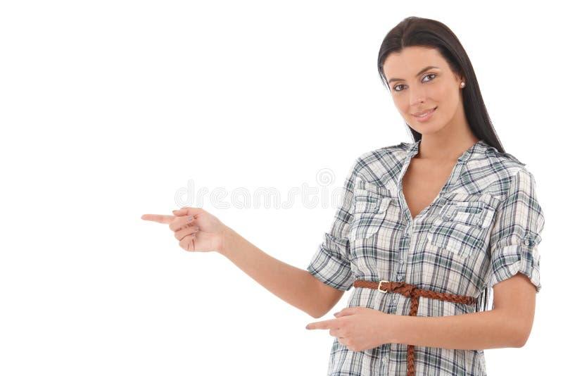 Härlig kvinna som pekar till höger le fotografering för bildbyråer
