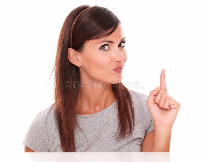 Härlig kvinna som pekar upp, medan undra royaltyfri fotografi