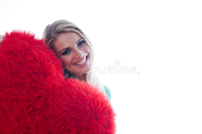Härlig kvinna som plirar rundan en röd hjärta royaltyfri foto