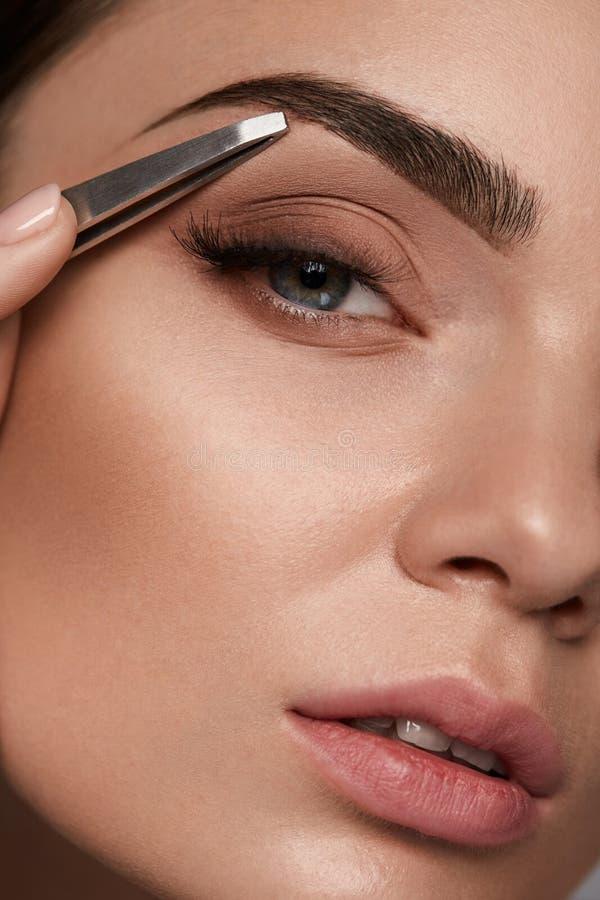 Härlig kvinna som plockar ögonbryn Skönhetkrönkorrigering royaltyfri bild