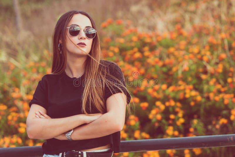 Härlig kvinna som poserar i blommafält med korsade armar arkivbild
