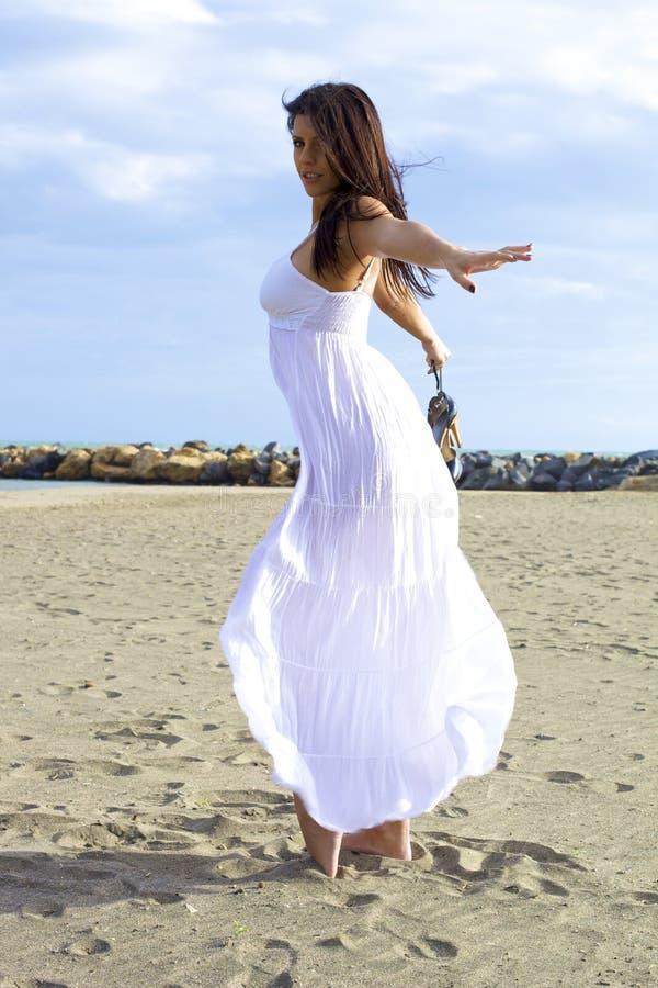 Härlig kvinna som poserar och dansar på sanden royaltyfri fotografi