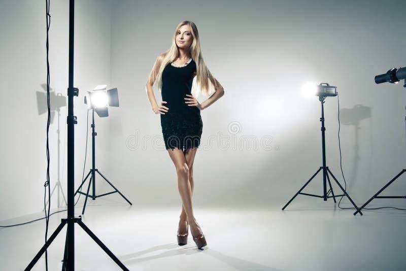 Härlig kvinna som poserar på studion i ljusa exponeringar arkivbilder