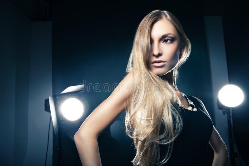 Härlig kvinna som poserar på studion i ljusa exponeringar royaltyfria bilder