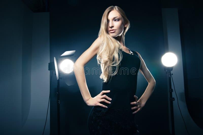 Härlig kvinna som poserar på studion i ljusa exponeringar royaltyfri foto