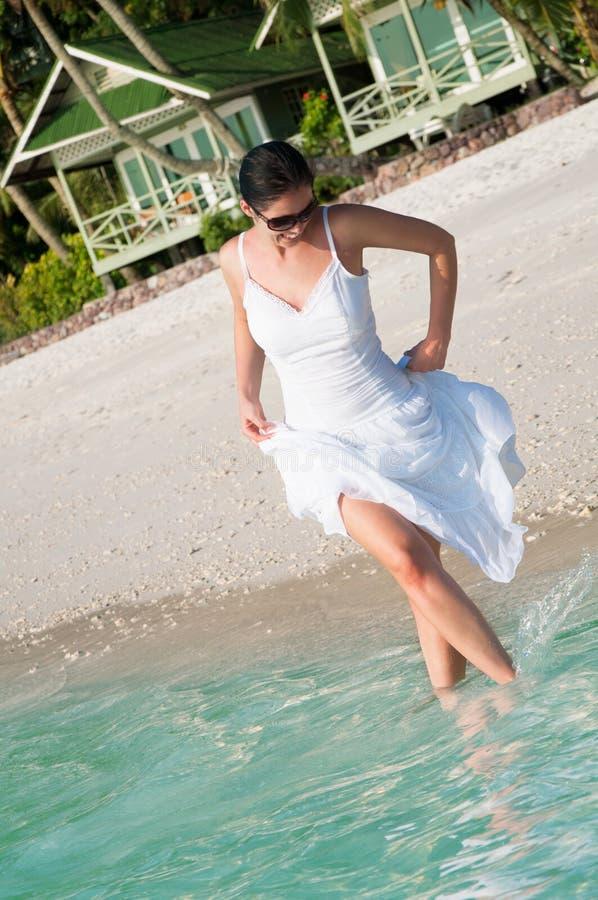Härlig kvinna som promenerar sjösidan på den tropiska stranden arkivbilder