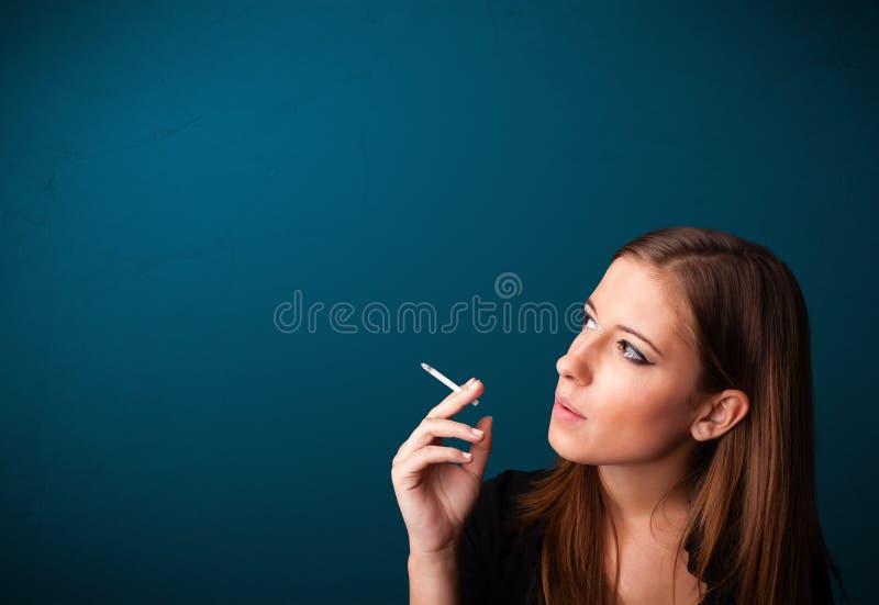 Härlig kvinna som röker kopieringsutrymme för cigarett vith royaltyfri bild