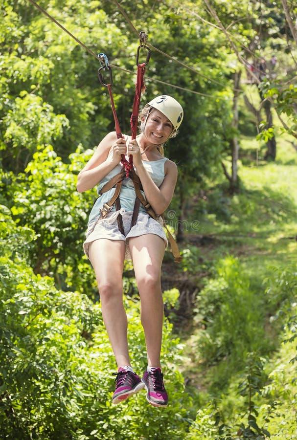 Härlig kvinna som rider en vinandelinje i en frodig tropisk skog royaltyfri foto