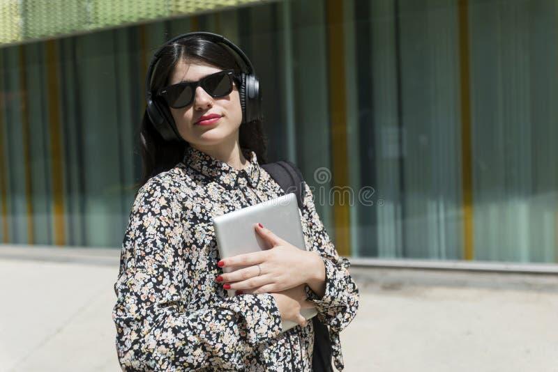 Härlig kvinna som rymmer en digital minnestavla, medan stå i set arkivbilder