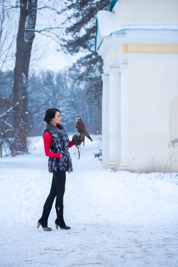 Härlig kvinna som rymmer en falk arkivfoton