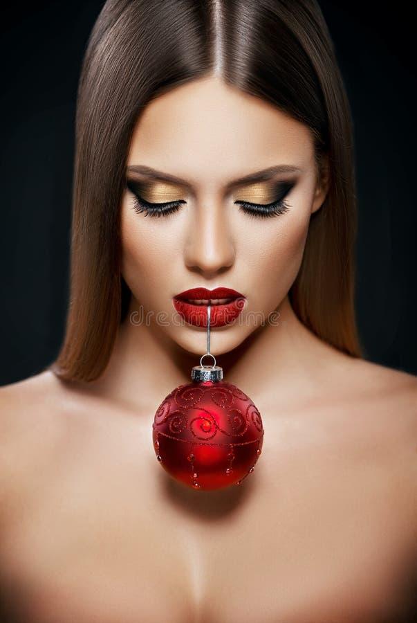Härlig kvinna som rymmer en julprydnad med tänder över mörk bakgrund fotografering för bildbyråer
