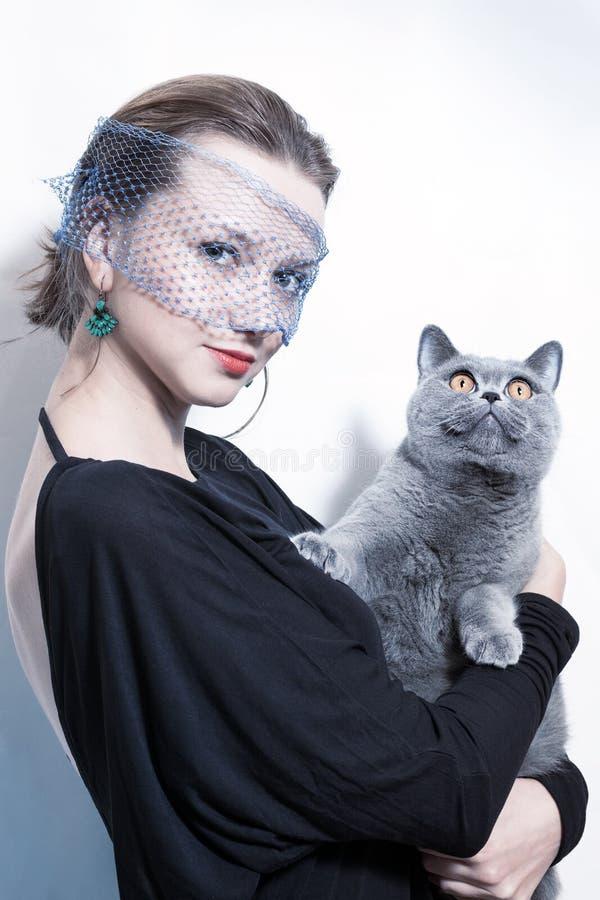 Härlig kvinna som rymmer en katt i henne armar royaltyfri bild