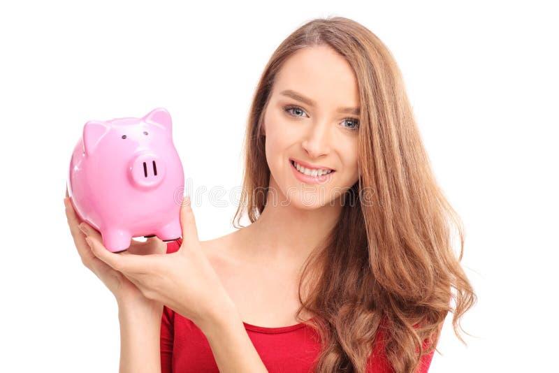 Härlig kvinna som rymmer en piggybank arkivfoton