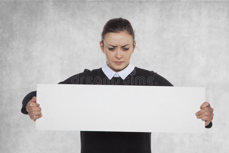 Härlig kvinna som rymmer en tom affischtavla, kopieringsutrymme arkivfoton