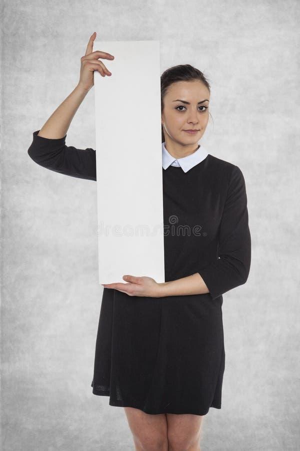 Härlig kvinna som rymmer en tom affischtavla, utrymme för ANNONS royaltyfria foton