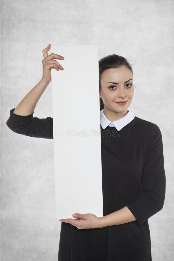 Härlig kvinna som rymmer en tom affischtavla, utrymme för annonsering arkivfoton