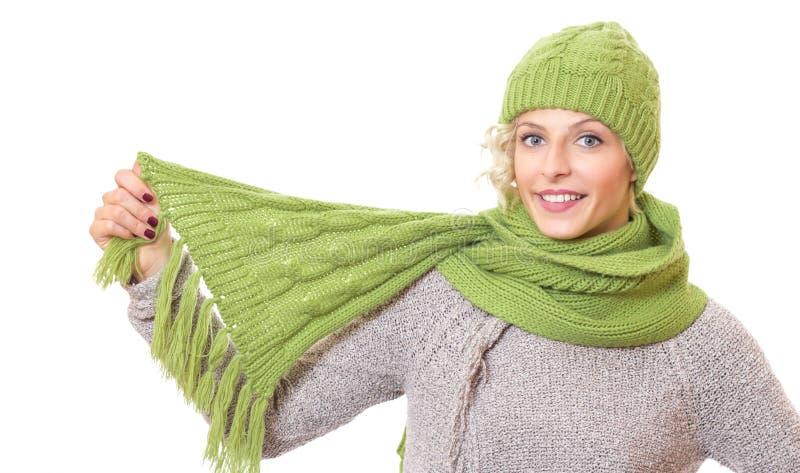 Härlig kvinna som rymmer hennes halsduk och varmt bär locket arkivfoto