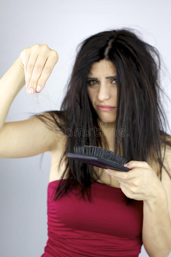 Härlig kvinna som rymmer långt hår från att borsta för hårt arkivbild