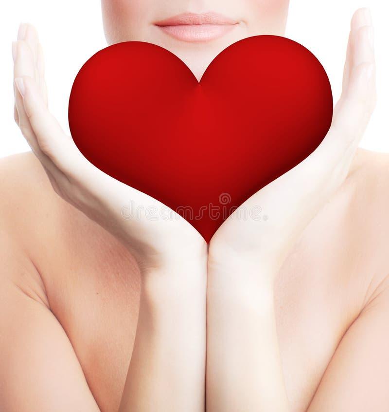 Härlig kvinna som rymmer stor röd hjärta royaltyfri foto
