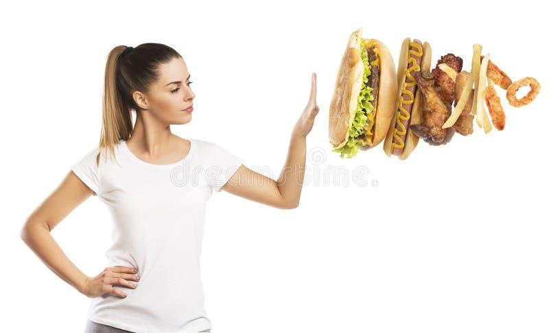 Härlig kvinna som säger INTE till sjuklig mat arkivfoto