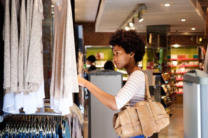 Härlig kvinna som söker efter kläder i lager arkivbild