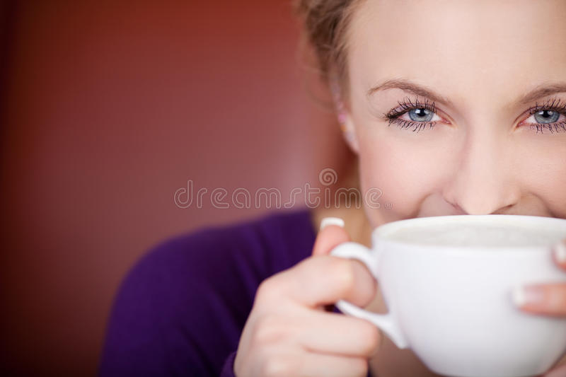 Härlig kvinna som ser över en kopp kaffe royaltyfri foto