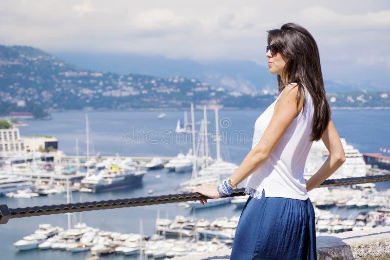 Härlig kvinna som ser den Monte - carlo hamnen i Monaco Azur Coast arkivfoto