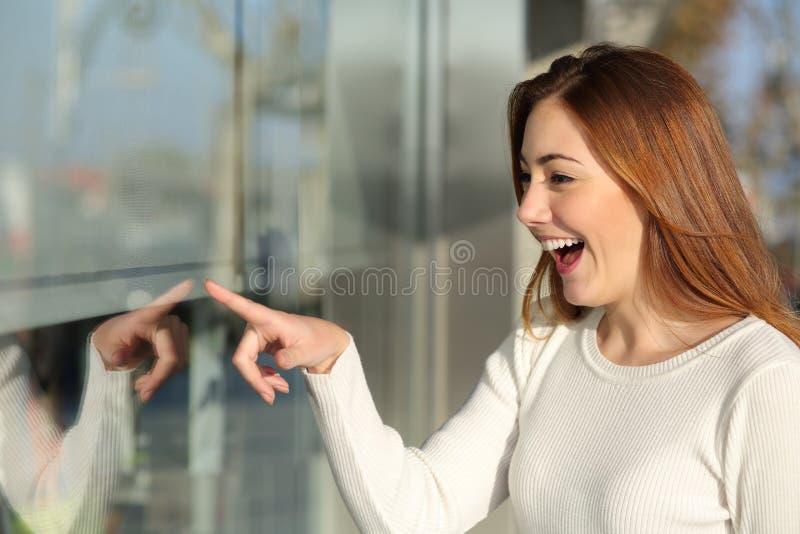 Härlig kvinna som ser en förvånad skyltfönster arkivfoto