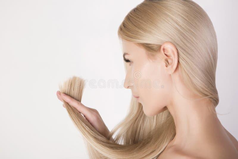 Härlig kvinna som ser på hennes sunda hårslut och nya frisyr royaltyfria bilder