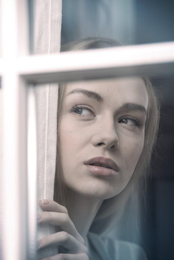 Härlig kvinna som ser vid fönstret royaltyfri fotografi