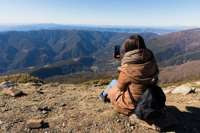 Härlig kvinna som sitter, når att ha fotvandrat och att ha tagit fotoet med telefonen under vinter eller höst i Catalonia arkivbild