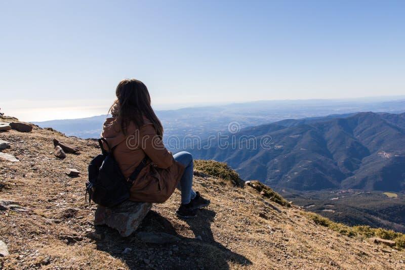 Härlig kvinna som sitter, når att ha fotvandrat under vinter eller höst i Catalonia & x28; Turo del Home - Spanien arkivfoton